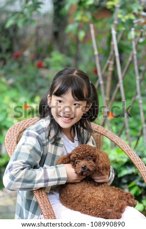Asian kid sitting and holding poodle dog - stock photo