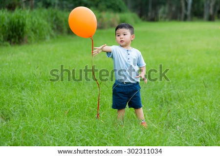 Asian kid want to catch with balloon at outdoor - stock photo