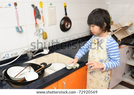 Asian kid washing the dishes in the kitchen - stock photo