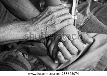 asian kids little boy hand touches and holds an old man wrinkled hands. - stock photo