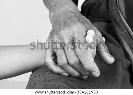 asian kids little boy  touches and holds hand old man ,black and white tone