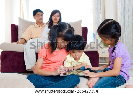 Asian kids playing tablet computer