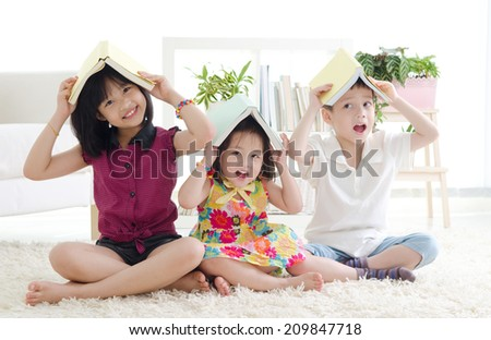 Asian kids putting books on their head