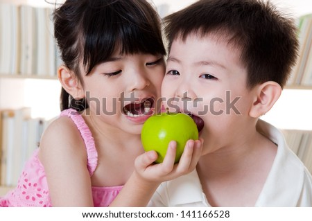 Asian kids sharing an apple - stock photo