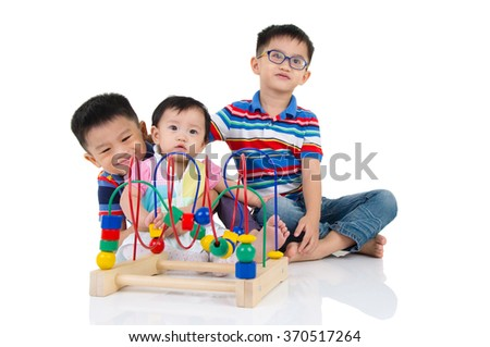 Asian kids sitting on the floor, playing with toy. - stock photo