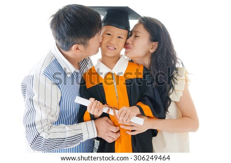 Asian kindergarten child in graduation gown and mortarboard kissed by his parent during graduation - stock photo