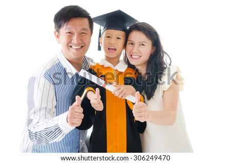 Asian kindergarten kid in graduation gown and mortarboard - stock photo