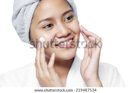 Asian lady applying facial cream. Isolated in white background.