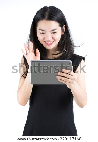 Asian lady chatting using a tablet - stock photo