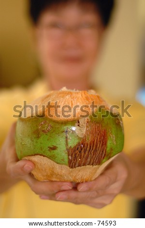 Asian lady holding up a coconut drink