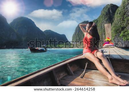 Asian lady relax on long tail boat at maya beach, Phi Phi island near Phuket in Thailand - stock photo