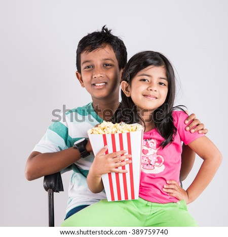 asian little boy and girl watching movie with pop corn, little indian girl sitting with brother watching movie eating popcorn, indian kids eating pop corn, kids watching movie with pop corn