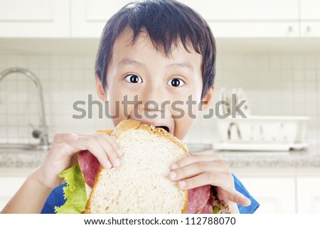 Asian little boy eating big sandwich. shot in the kitchen - stock photo