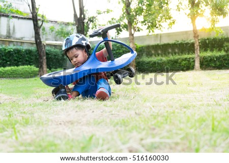 Asian little boy playing in the  garden with swing car