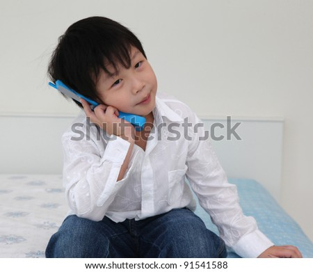 Asian little boy playing phone on bed room