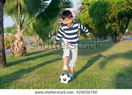 Asian little boy playing soccer in the park