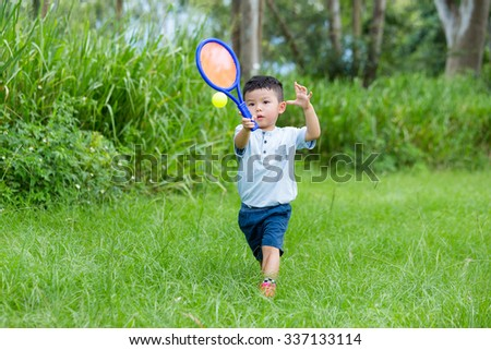 Asian little boy playing tennis at outdoor - stock photo