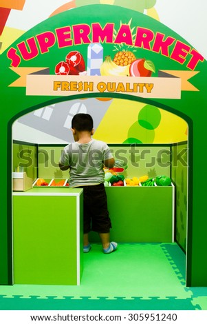 Asian little boy role playing at a vege store. - stock photo
