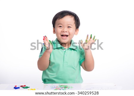 Asian little boy with hands in the paint. Asian schoolboy showing his painted palms - stock photo