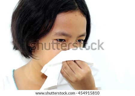 Asian little child girl sneezing in a tissue when runny nose and cough