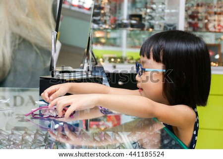 Asian Little Chinese Girl Choosing Glasses at Optics Store - stock photo