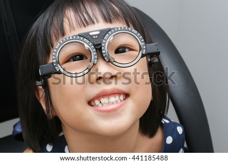Asian Little Chinese Girl Doing Eyes Examination at An Optical Shop - stock photo