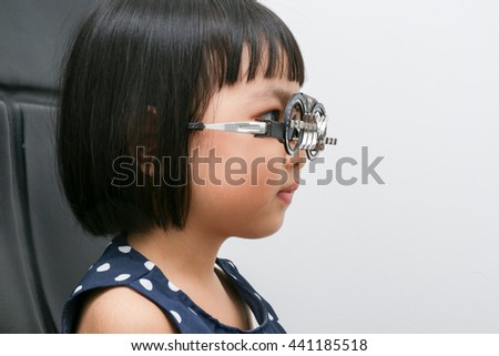 Asian Little Chinese Girl Doing Eyes Examination in isolated White Background - stock photo