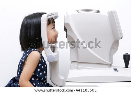 Asian Little Chinese Girl Doing Eyes Examination Through Auto refraktometer in isolated White Background
