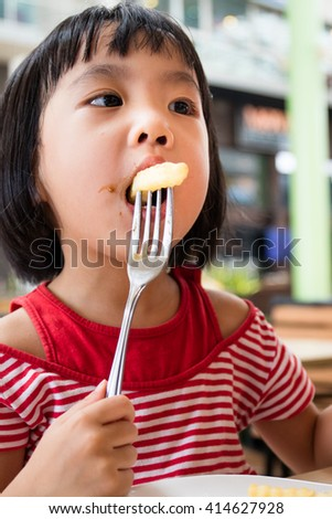 Asian Little Chinese Girl Eating French Fries in Outdoor Cafe