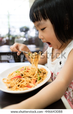 Asian Little Chinese Girl Eating spaghetti in Outdoor Cafe - stock photo