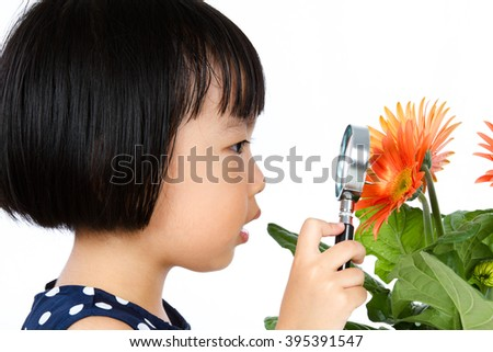 Asian Little Chinese Girl Looking at Flower through a Magnifying Glass isolated on White Background
