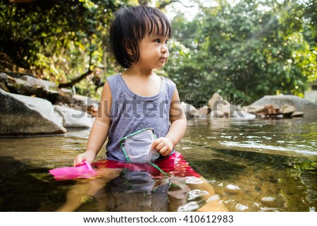 Asian Little Chinese Girl Playing in Creek in the Forest