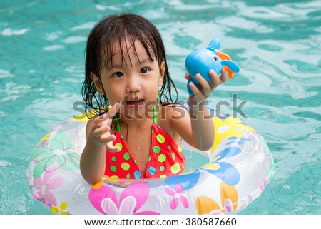 Asian Little Chinese Girl Playing in Swimming Pool with Swimming Circle - stock photo