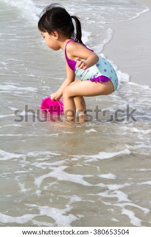 Asian Little Chinese Girl Playing Sand with Beach Toys on Tropical Beach