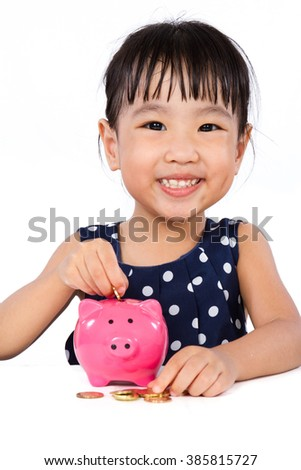 Asian Little Chinese Girl Putting Coins into Piggy Bank isolated on White Background