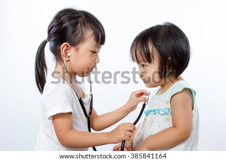 Asian Little Chinese Girls Playing as Doctor and Patient with Stethoscope isolated on white background