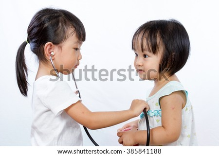 Asian Little Chinese Girls Playing as Doctor and Patient with Stethoscope isolated on white background - stock photo