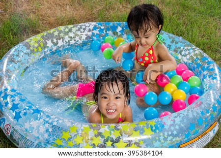 Asian Little Chinese Girls Playing in an Inflatable Rubber Swimming Pool Outdoors - stock photo
