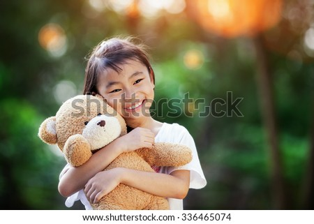 Asian Little cute girl standing in the grass holding large teddy bear with sunset light - stock photo