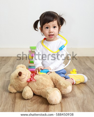 Asian little doctor girl play with toy teddy bear in the room.