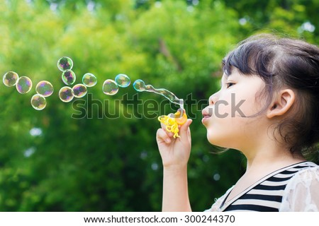 Asian little girl blowing soap bubbles in green park - stock photo
