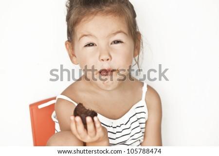 Asian little girl eating chocolate - stock photo