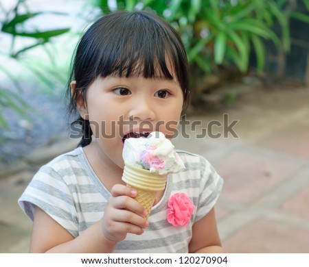 asian little girl eating ice cream, happiness moment - stock photo