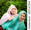 Asian little girl enjoying the rain dressed in a raincoat with her mother - stock photo