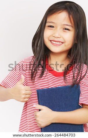 Asian little girl holding a big book. Isolated on white background