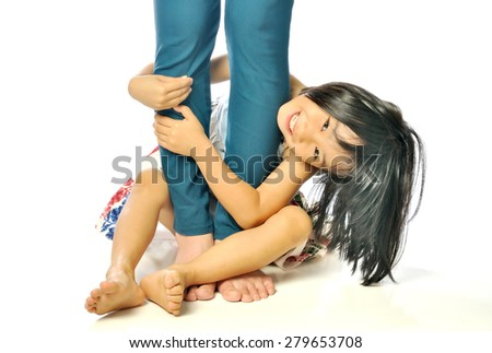 Asian little girl hugging mother's leg and playing on white background - stock photo