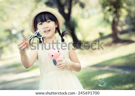 Asian little girl is blowing a soap bubbles with smile face in park with vintage style - stock photo