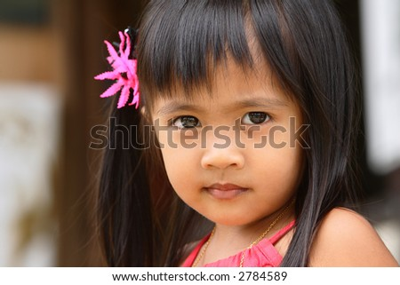 Asian little girl outdoor with flower in her hair - stock photo