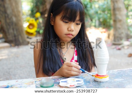 Asian little girl painting in the park