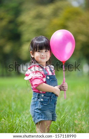 Asian little girl playing balloon in the garden - stock photo